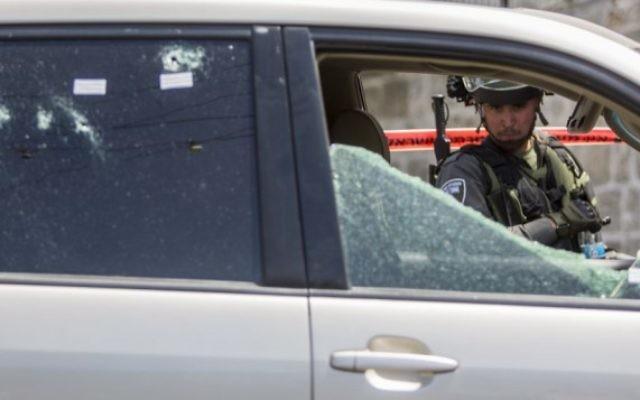 Un policier regarde la voiture utilisée par le suspect pour foncer sur des policiers des frontières dans le quartier arabe d'A-Tur à Jérusalem-Est, le 20 mai 2015. (Crédit : Yonatan Sindel / Flash90)