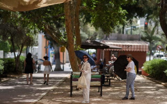 Des Israéliens utilisent des parapluies pour conjurer le fort soleil d'été sur le Boulevard Rothschild au centre  de Tel Aviv pendant une forte vague de chaleur qui a frappé le pays le 27 mai 2015  (Crédit photo: Ben Kelmer / Flash90)