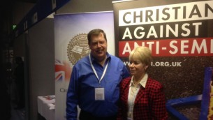 """Des volontaires chrétiens à l'Exposition Christian Resources de mai 2015 à côté d'une bannière arborant le slogan """"Chrétiens contre l'antisémitisme"""" la  première campagne britannique de CUFI (Jenni Frazer / The Times of Israel)"""