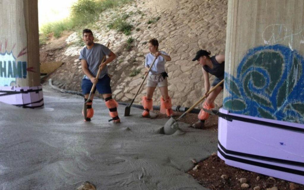 Des travailleurs coulant du ciment temporaire pour les fondations du 'Point de Rencontre' (Jessica Steinberg / Times of Israel)