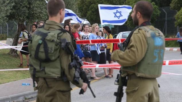 Les soldats israéliens se tiennent devant des jeunes juifs manifestant avec des drapeaux israéliens sur les lieux de l'attaque bélier près Alon Shvut à Gush Etzion, le 14 mai 2015 (Crédit : Nati Shohat / Flash90)