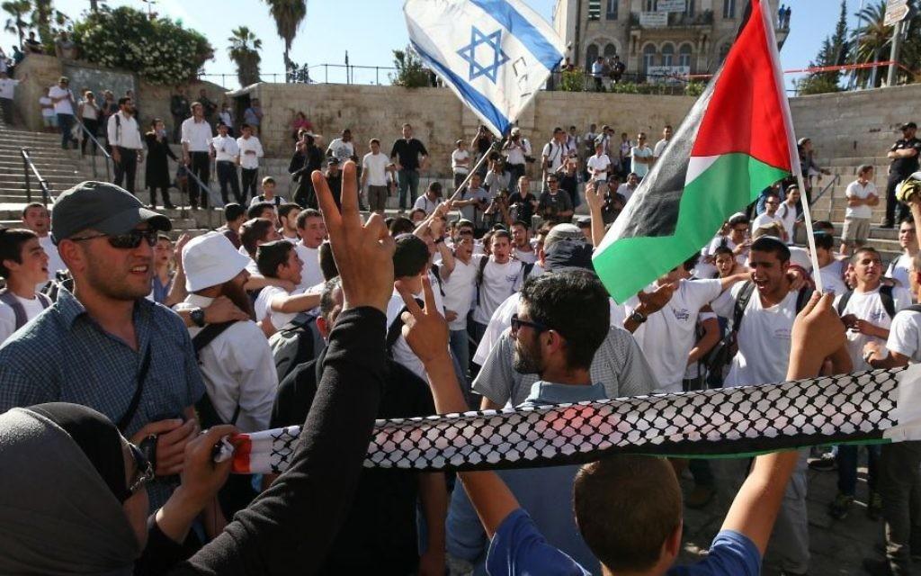 Des Palestiniens protestent tandis que des adolescents  juifs célèbrent la Journée de Jérusalem, Porte de Damas, dans la Vieille Ville de Jérusalem, 17 mai 2015. (Crédit : Nati Shohat / Flash90]