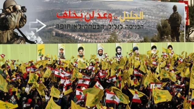 """Des partisans du Hezbollah libanais dans la ville méridionale de Nabatiyeh, le 24 mai 2015, regardant une allocution télévisée du chef du mouvement Hassan Nasrallah. Une pancarte indique en arabe et en hébreu: """"L'invasion de la Galilée - la promesse ne sera pas brisée"""" (Mahmoud Zayat / AFP)"""