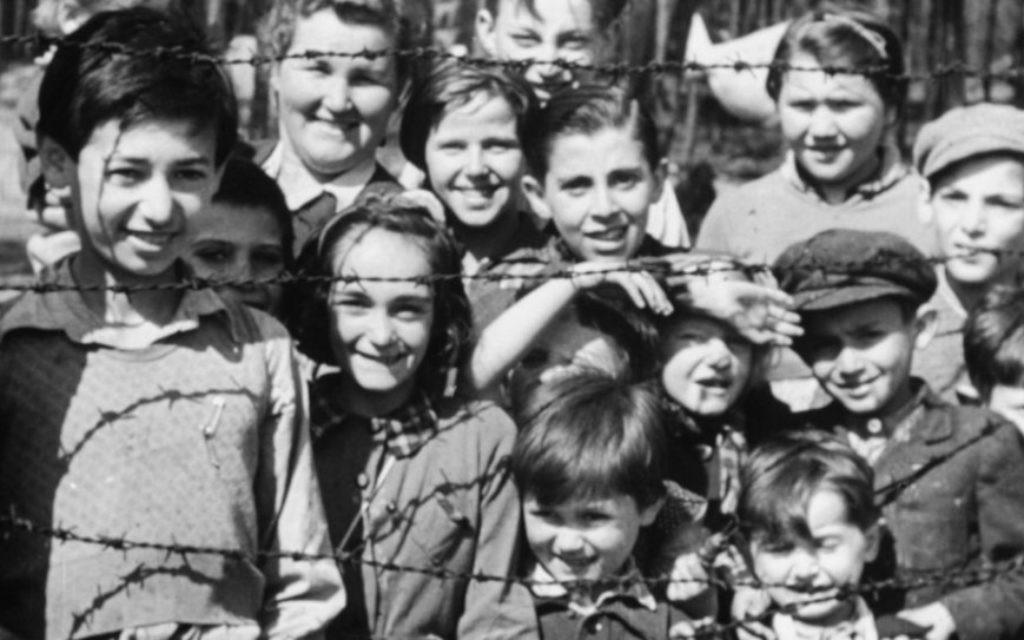 """Une photo extraite de """"L'enquête factuelle sur les camps de concentration allemands """" montrant des enfants souriants à travers les barbelés à l'arrivée les troupes alliées, avril 1945. (Imperial War Museum)"""