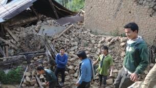 Les résidents de Kagatiguam dans les décombres de maisons plus haut dans le village le jeudi 30 avril 2015. (Crédit photo: Melanie Lidman / Times of Israel)