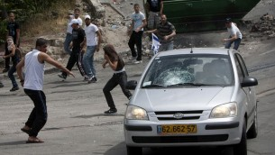 Des manifestants lançant des pierres sur une voiture dans le quartier de Silwan à Jérusalem en 2011. (Crédit photo: Yonatan Sindel / Flash90)