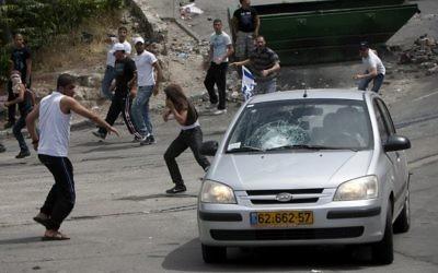 Des manifestants lançant des pierres sur une voiture dans le quartier de Silwan, à Jérusalem Est, en 2011. (Crédit : Yonatan Sindel/Flash90)