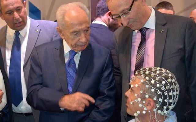L'ancien président Shimon Peres se renseigne sur la technologie ElMindA lors de la Conférence du Président de 2013, à Jérusalem. (Crédit : Courtesy ElMindA)
