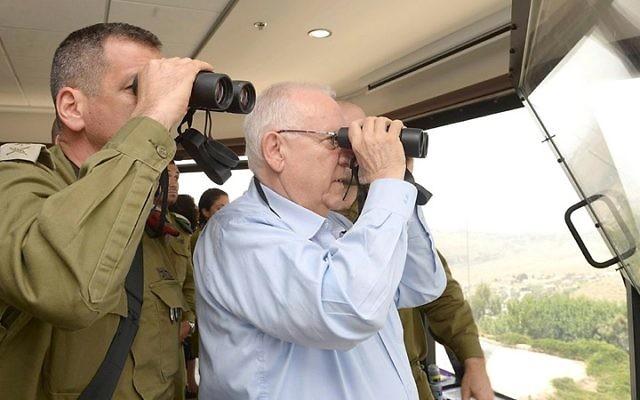 Le président Reuven Rivlin regarde à travers des jumelles pendant une visite à la frontière du district Nord d'Israël, le 27 mai 2015. (Crédit : Mark Neyman / GPO)