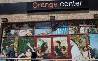 Des Israéliens passant devant un magasin de l'opérateur de télécommunications Partner, qui dispose d'une licence de la société française Orange pour utiliser sa marque, à Jérusalem le 4 juin 2015 (Crédit : AFP PHOTO / MENAHEM KAHANA)