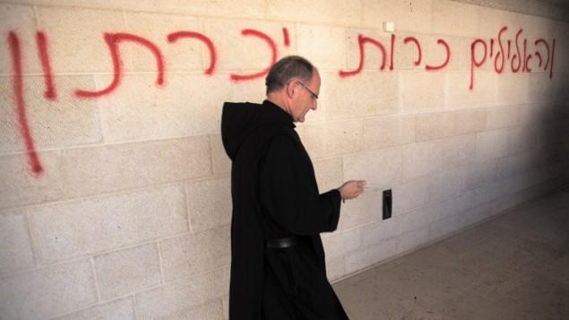 """Un prêtre marche à côté des graffitis en hébreu : """" les fausses idoles seront éliminées"""", à l'église de la Multiplication à Tabgha, sur les rives de la mer de Galilée dans le nord d'Israël, le 18juin 2015 (Crédit : AFP / Menahem Kahana)"""