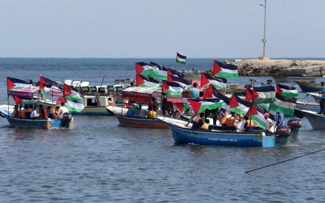 Les Palestiniens brandissent leur drapeau national lors d'un rassemblement pour montrer leur soutien aux militants à bord d'une flottille qui mettent le voile pour Gaza pour tenter de briser le blocus israélien sur Gaza, dans le port de Gaza ville, le 24 juin 2015 (Crédit : AFP / Mahmud Hams)