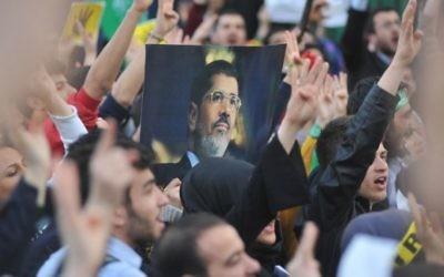 Les partisans des Frères musulmans avec un portrait du président déchu Mohammed Morsi tandis qu'ils prennent part à un rassemblement pour protester contre les peines de mort pour des membres du groupe radical en Egypte, devant l'ambassade égyptienne à Ankara le 9 avril 2014 (Crédit : AFP PHOTO / ADEM ALTAN)