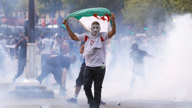Un manifestant avec un masque de Guy Fawkes et un drapeau algérien lors d'affrontements avec les agents anti-émeute de la police française, place de la République à Paris, suite à l'interdiction d'une manifestation contre l'opération militaire israélienne à Gaza et pour soutenir l'Autorité palestinienne le 26 juillet 2014 (Crédit : Kenzo Triboillard / AFP)
