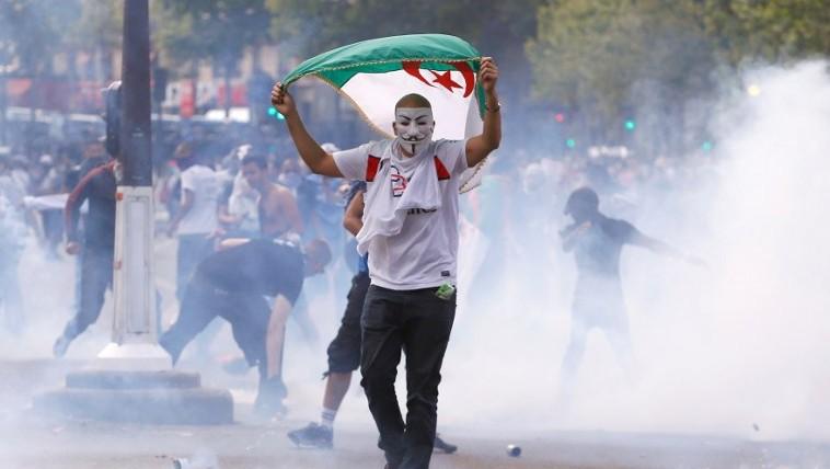 Un manifestant portant un masque de Guy Fawkes et agitant un drapeau algérien lors d'un affrontements avec les agents anti-émeute de la police française, sur la place de la République à Paris, à la suite d'une manifestation interdite contre l'opération militaire israélienne à Gaza et pour soutenir l'Autorité palestinienne le 26 juille, 2014 (Crédit : Kenzo Triboillard / AFP)