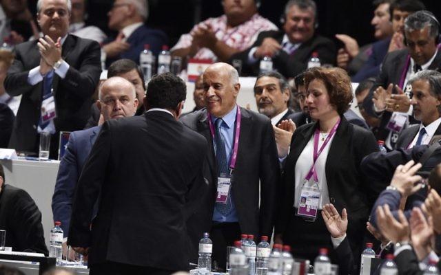 Ofer Eini (de dos), président et secrétaire général de l'Association de football d'Israël (IFA) serrant la main de Jibril Rajoub (au centre), président de la Fédération palestinienne de football lors du 65e Congrès de la FIFA à Zurich, le 29 mai 2015 (Crédit : AFP PHOTO / MICHAEL Buholzer)