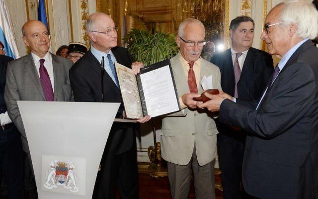 Yossi Gal (d) et Alain Juppé délivrent la médaille des Juste parmi les Nations à Jean-Pierre Fabre, fils de Suzon et Fernand Fabre, le 8 juin 2015 à Bordeaux. (Crédit : MEHDI FEDOUACH / AFP)