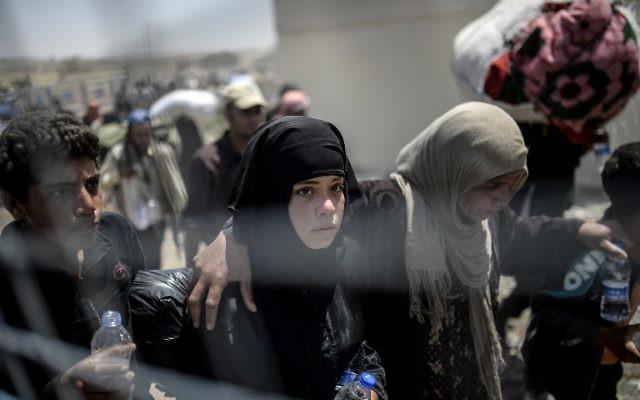 Les Syriens fuyant la guerre en se rendant au point de passage de la frontière Akcakale, dans la province de Sanliurfa, le 15 juin 2015. La Turquie a annoncé qu'elle prenait des mesures pour limiter le flux de réfugiés syriens sur son territoire après un afflux de milliers d'autres au cours des derniers jours en raison des combats entre les Kurdes et les djihadistes. En vertu d'une politique de « porte ouverte », la Turquie a accueilli près de 1,8 million de réfugiés syriens depuis le bébut du conflit en Syrie en 2011 (Crédit : AFP PHOTO / BULENT KILIC)