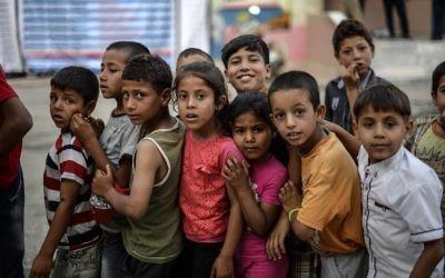 De jeunes enfants de réfugiés syriens font la queue pour la nourriture pour rompre le jeûne le 20 juin 2015 à Akcakale, dans la province de Sanliurfa, pendant le mois sacré du Ramadan. (Crédit : AFP)
