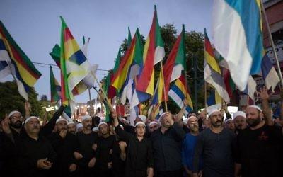 Les Druzes israéliens agitant des drapeaux lors d'une manifestation de quelque deux mille personnes dans  la ville druze de Daliyat al-Carmel, en Israël, appelant le gouvernement israélien à soutenir et à aider leurs frères de Syrie, le 14 juin 2015. (Crédit : AFP / MENAHEM KAHANA)