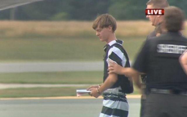 Dans une capture écran de WBTV News, le suspect Dylann Roof est escorté par la police avant son extradition vers Charleston. (Crédit : AFP/ WBTV NEWS/ HO)