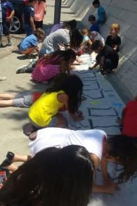Les étudiants et les enseignants faisant des panneaux le le 30 Juin 2015 pour recouvrir les graffitis racistes tagués sur les murs de leur école la veille. (Crédit : Autorisation Hand in Hand)