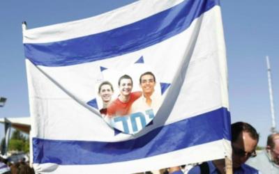 Drapeau israélien flanqué de l'image des trois adolescents assassinés et du mot hébreu « Yahad » (ensemble), lors de leur cérémonie funéraire conjointe, dans le cimetière de Modiin, le 1er juillet 2014. (Crédit : Yonatan Sindel / Flash90)