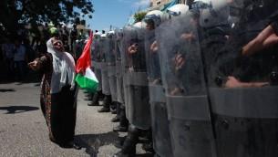 La police palestinienne en équipement anti-émeute empêche des partisans du Front Populaire pour la libération de la Palestine (FPLP) d'atteindre le siège du Président de l'AP, Mahmoud Abbas, dans la ville cisjordanienne de Ramallah, le 7 septembre 2013, lors d'une manifestation contre les négociations avec Israël. (Crédit : Issam Rimawi / Flash90)