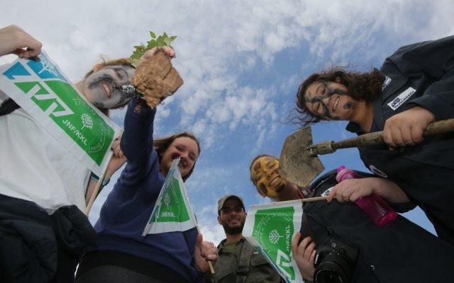 Des Israéliens brandissant des pancartes du Fonds national juif dans l'implantation cisjordanienne de Micmash, en janvier 2014. (Crédit : Yossi Zamir / flash 90)