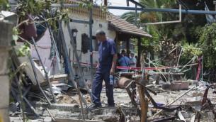 Un homme inspecte les dommages causés à une maison après une attaque à la roquette par des terroristes de la bande de Gaza sur la ville israélienne de Yehud, à côté de l'aéroport international Ben-Gurion d'Israël, le 22 juillet 2014. (Crédit : Yonatan Sindel / Flash90)