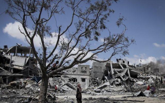 Des Palestiniens ramassent leurs effets dans les maisons détruites par les bombardements israéliens dans le nord de la bande de Gaza, à Beit Lahiya, le mardi 4 août 2014. (Crédit : Emad Nasser / Flash90)