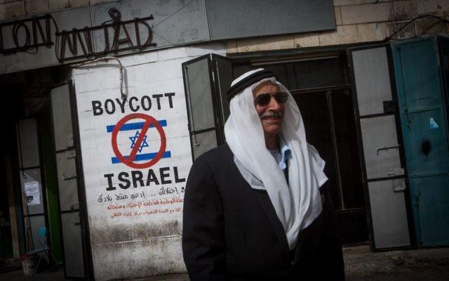 Un Palestinien marche près d'un graffiti demandant le boycott d'Israël dans la ville de Bethléem en Cisjordanie 11 février 2015 (Crédit : Miriam Alster / Flash90)