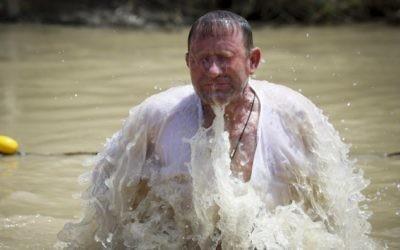 Un pèlerin chrétien orthodoxe prend un bain dans le Jourdain, dans le cadre d'une cérémonie de baptême traditionnelle sur le site de Qasr el Yahud, l'endroit où l'on pense que Jésus a été baptisé, près de la ville de Jéricho, en Cisjordanie, le 11 avril 2015. (Crédit : Maxim Dinshtein / Flash90)