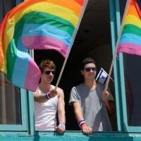 Des hommes agitant des drapeaux à la Gay Pride de Tel-Aviv le 12 juin 2015. (Crédit : Flash90 / Gili Yaar)