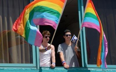 Des hommes agitant des drapeaux à la Gay Pride de Tel-Aviv le 12 juin 2015 (Crédit : Flash90 / Gili Yaar)