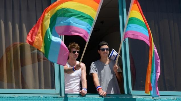 Des Hommes agitant drapeaux à la Gay Pride Parade annuel de Tel-Aviv le 12 juin 2015 (Crédit : Flash90 / Gili Yaar)