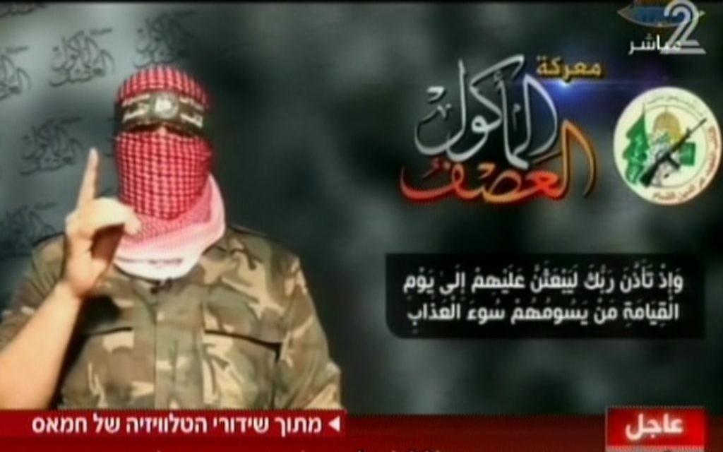 Abu Obeida, le porte-parole du Hamas à la télévision, le 20 août 2014 ; à gauche du logo de l'aile militaire du Hamas  (Crédit : Capture d'écran Deuxième chaîne)