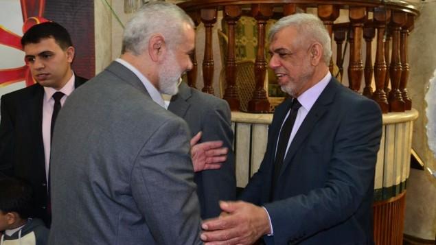 Le journaliste basé à Gaza Mustafa Sawwaf (à droite) serrant la main de l'ancien Premier ministre du Hamas, Ismail Haniyeh en mars 2015 (Crédit : Page Facebook de Mustafa Sawwaf)