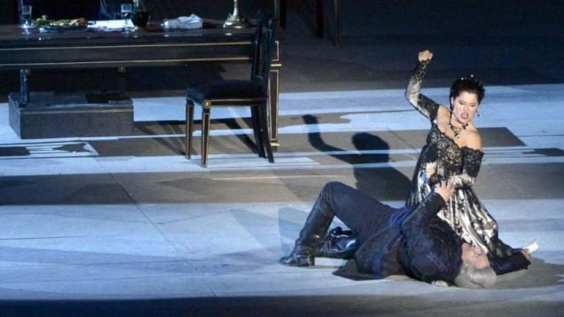 Moment de passion : Tosca tue Scarpio, qui a emprisonné et torturé son amant, avec un couteau de table (Crédit : Autorisation d'Israël Opéra / Yossi Zwecker)