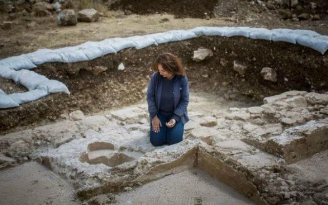 Annette Nagar, de l'Autorité des antiquités, regarde les fonts baptismaux de l'église de l'époque byzantine découverte à Abu Ghosh lors des travaux d'agrandissement et de modernisation de l'autoroute Jérusalem-Tel Aviv, en juin 2015 (Yonatan Sindel / Flash90)