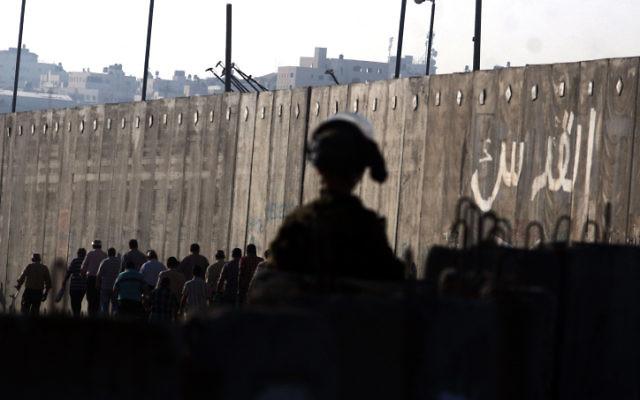 Un soldat de Tsahal observe des Palestiniens qui traversent le poste de contrôle de Qalandiya près de la ville de Ramallah en Cisjordanie (Crédit : Issam Rimawi / Flash90)