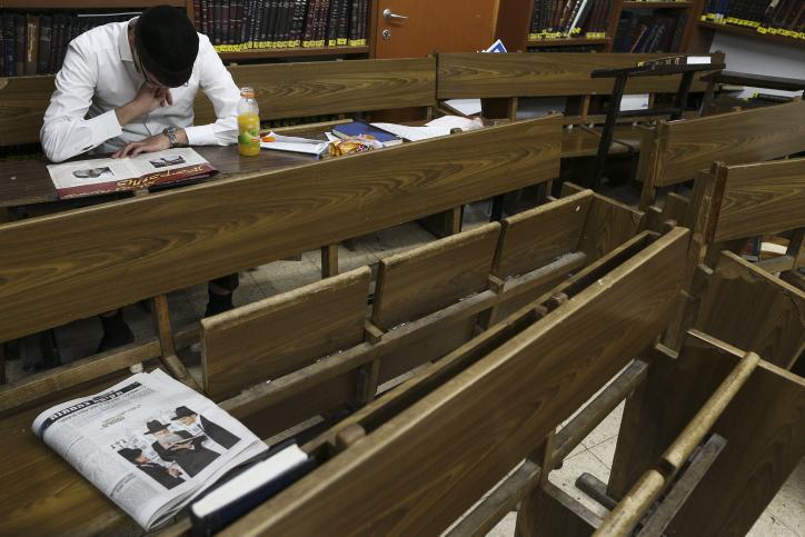 Un jeune homme juif ultra-orthodoxe en train de lire un journal entre deux cours à la Yeshiva Ateret Israël, à Jérusalem le 2 septembre 2013 (Crédit : Nati Shohat / FLASH90)