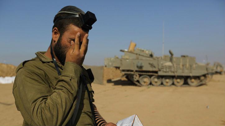 Un soldat israélien prie à une zone de transit de Tsahal près de la frontière israélienne avec Gaza, le 31 juillet 2014 (Crédit : Yaakov Naumi / FLASH90)