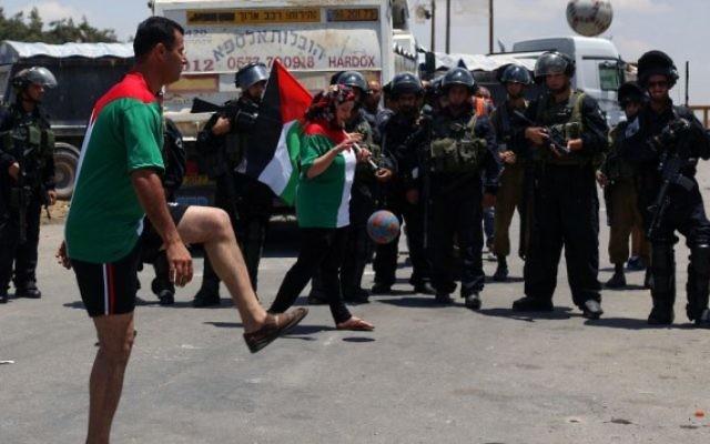 Photo illustrative de Palestiniens jouant au football en solidarité pour les prisonniers de la faim devant la prison d'Ofer en Cisjordanie, le 11 juin 2014. (Issam Rimawi / Flash90)
