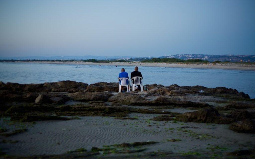 Sur la plage de Jisr az-Zarqa, après le coucher du soleil, avec le Kibbutz Maagan Michael au loin. (Crédit : Eliyahu Kamisher)