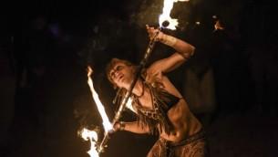 Une participante du Midburn tournoie avec un bâton enflammé lors du deuxième festival annuel, qui est calqué  sur le Burning Man d'Amérique, le 24 mai 2015 (Crédit photo: Ben Kelmer / Flash90)