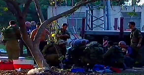 Les premiers intervenants et les soldats de Tsahal à l'endroit où un mortier a atérri dans le kibboutz Nirim dans la région d'Eshkol. (Crédit : Capture d'écran Deuxième chaîne)