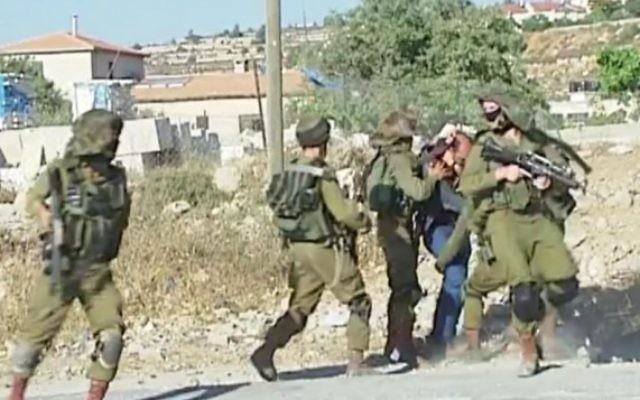 Un Palestinien battu et retenu par des soldats israéliens lors d'une manifestation violente dans le camp de réfugiés de Jelazoun, près de Ramallah, le 12 juin 2015 (Capture d'écran: Télévision palestinienne)