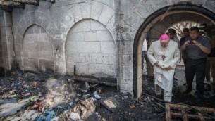 Un prêtre inspecte les dommages causés à l'Eglise de la Multiplication, à Tabgha, sur le lac de Tibériade, qui a  pris feu dans ce que la police suspecte être un incendie criminel, 18 juin 2015 (Crédit photo: Basel Awidat / Flash90)