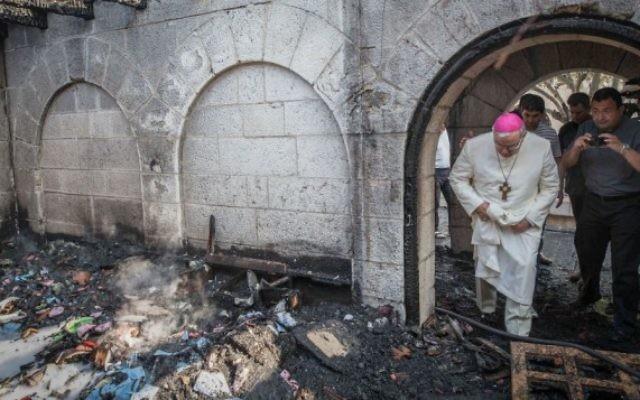 Un prêtre inspecte les dommages causés à l'Eglise de la Multiplication, à Tabgha, sur le lac de Tibériade, qui a  pris feu dans ce que la police suspecte être un incendie criminel, 18 juin 2015 (Crédits : Basel Awidat / Flash90)
